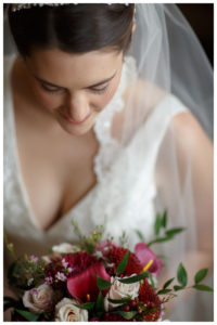 Wedding day bridal portrait with bride looking down at flower bouquet