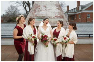 Bride and Bridesmaids laughing on the upper deck in front of the fireplace at the Inn on Boltwood