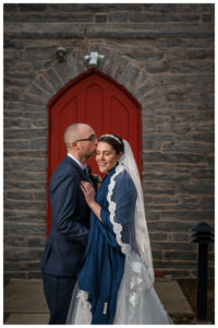 Bride and groom portrait in front of red door across from the Inn on Boltwood