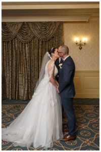 Bride and groom first kiss at the end of wedding ceremony in ballroom at the Inn on Boltwood