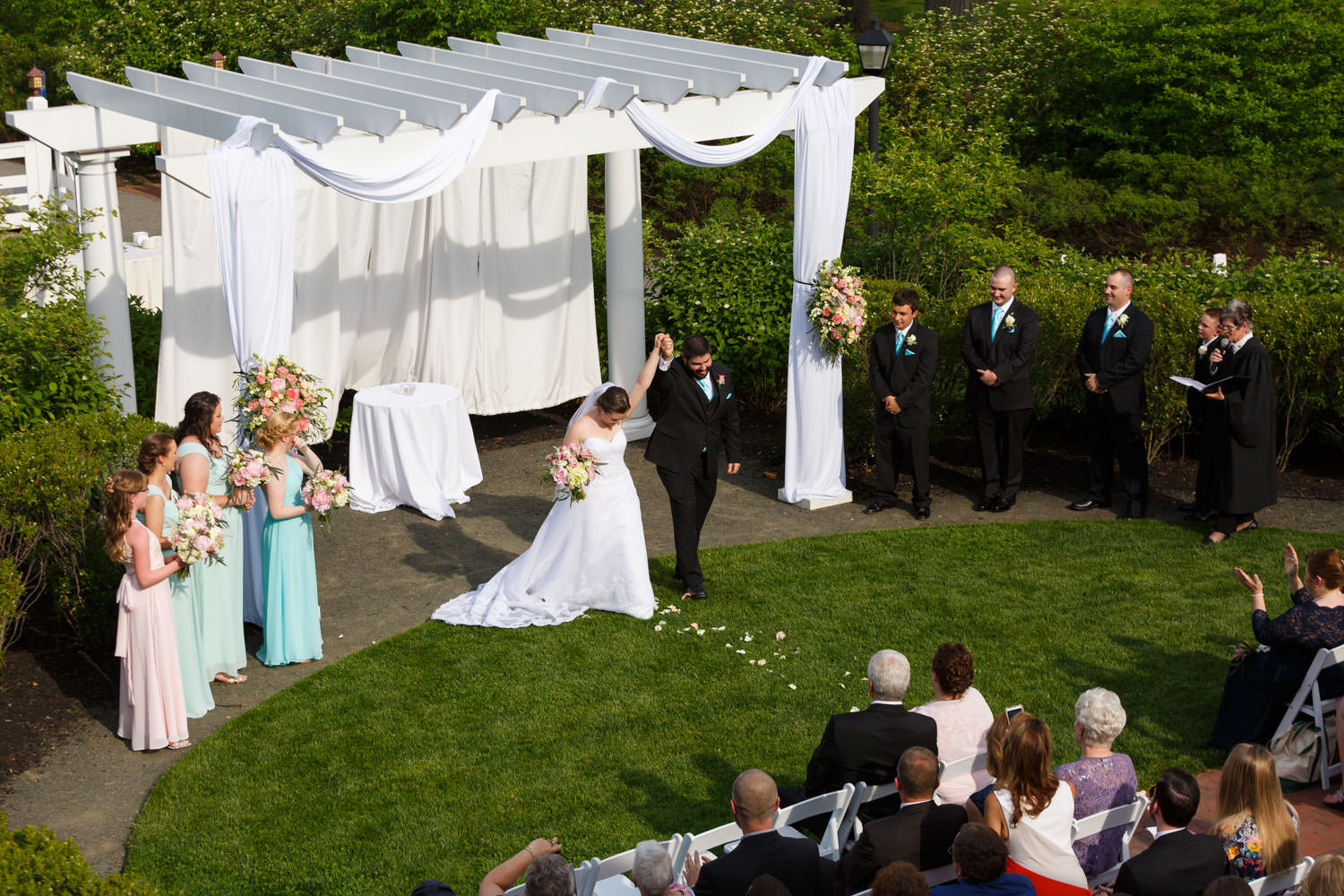 Bride and groom holding hands up in the air during recessional