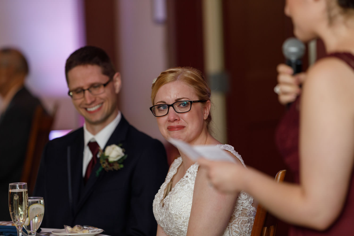Bride tearing up during maid of honor speech during reception with groom laughing in background