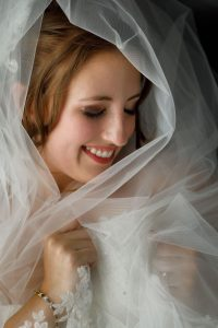 Portrait of bride with veil framing her face, eyes closed and smiling.