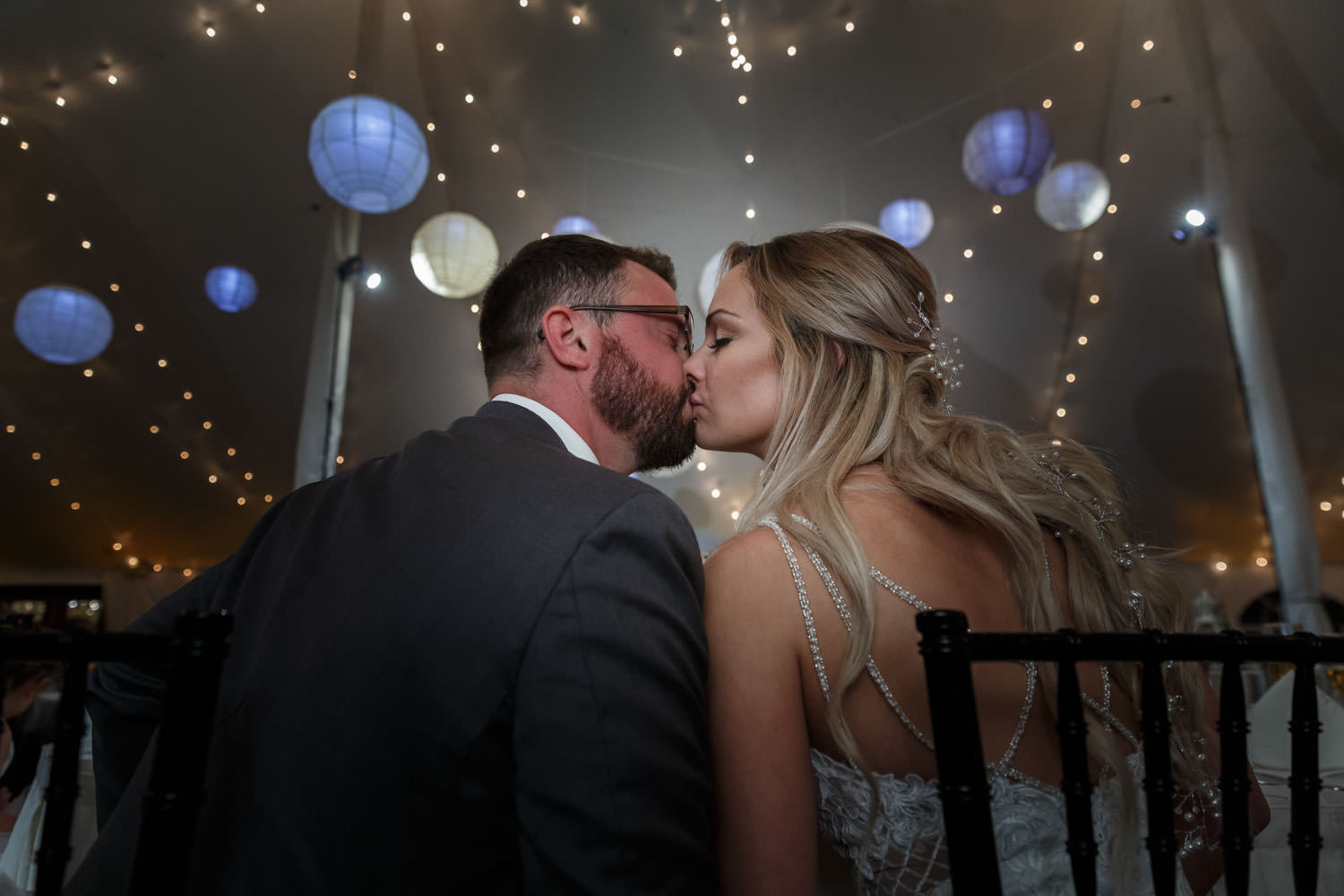 Bride and groom kissing with photo taken from behind couple with Chinese lanterns hanging in the background
