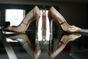 Reflection of Brides sparkling shoes with wedding dress hanging in the window