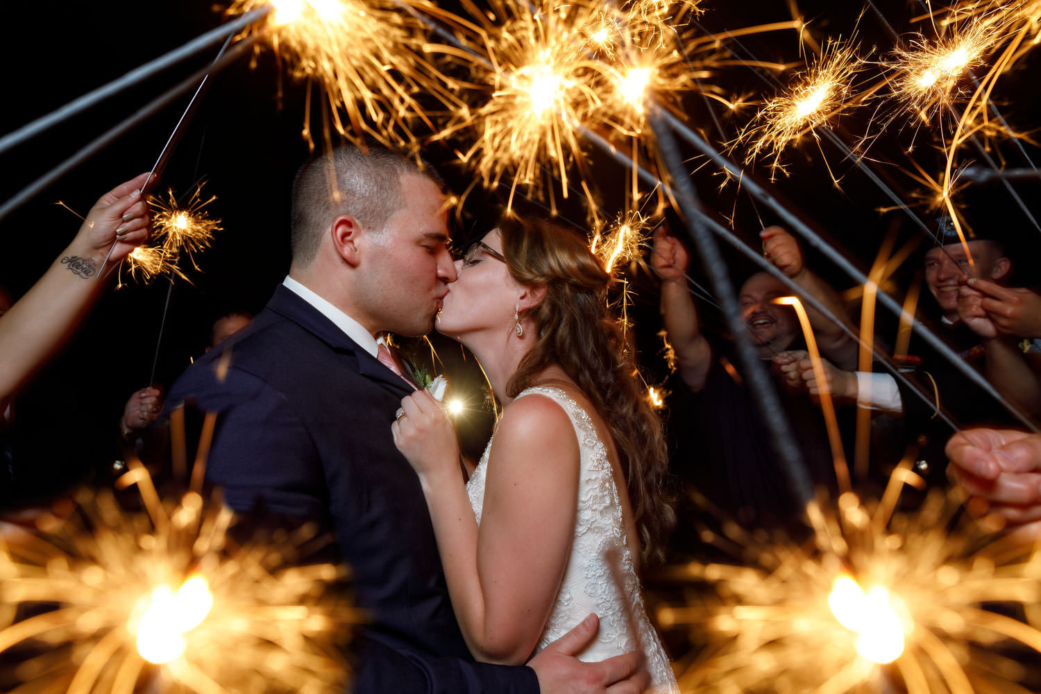 Night time with Bride and Groom Kissing with wedding guests with sparklers around the couple
