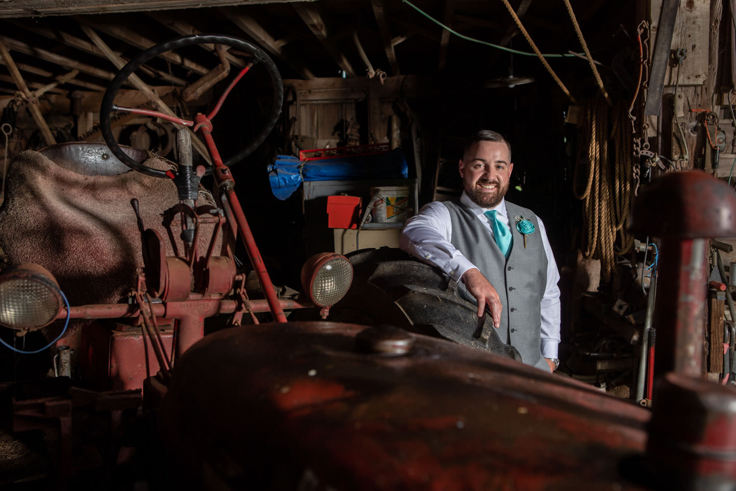 Groom leaning on tractor tire in barn