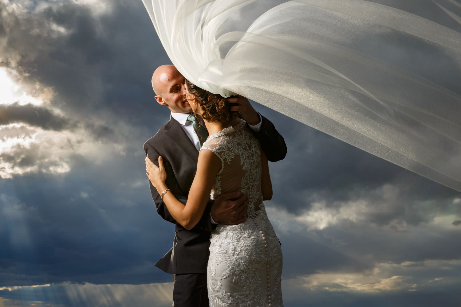 Bride and Groom with brides veil blowing in the wind with ominous sky behind them
