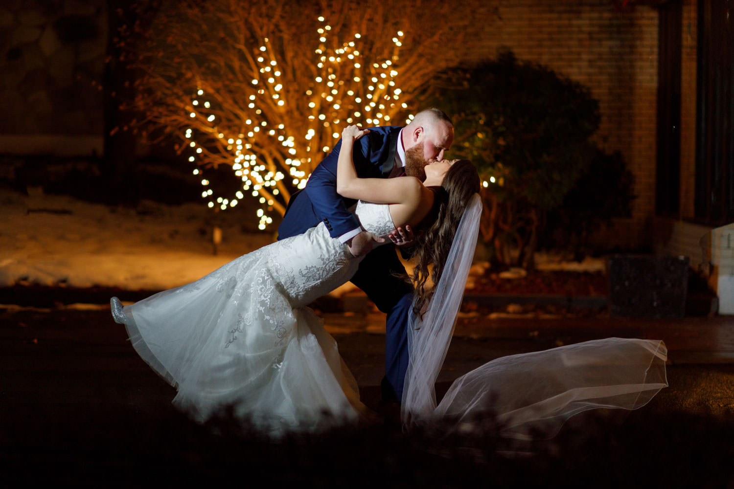Bride dipping groom with twinkle lights in background