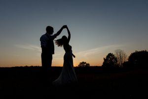 Groom twirling bride with sunset in background silhouette photo
