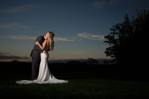 Romantic photo of bride and groom in sunset background