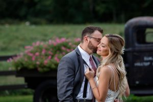 Groom kissing brides cheek while she pulls lightly on his suspenders with Zukas Hilltop Barn Truck in background