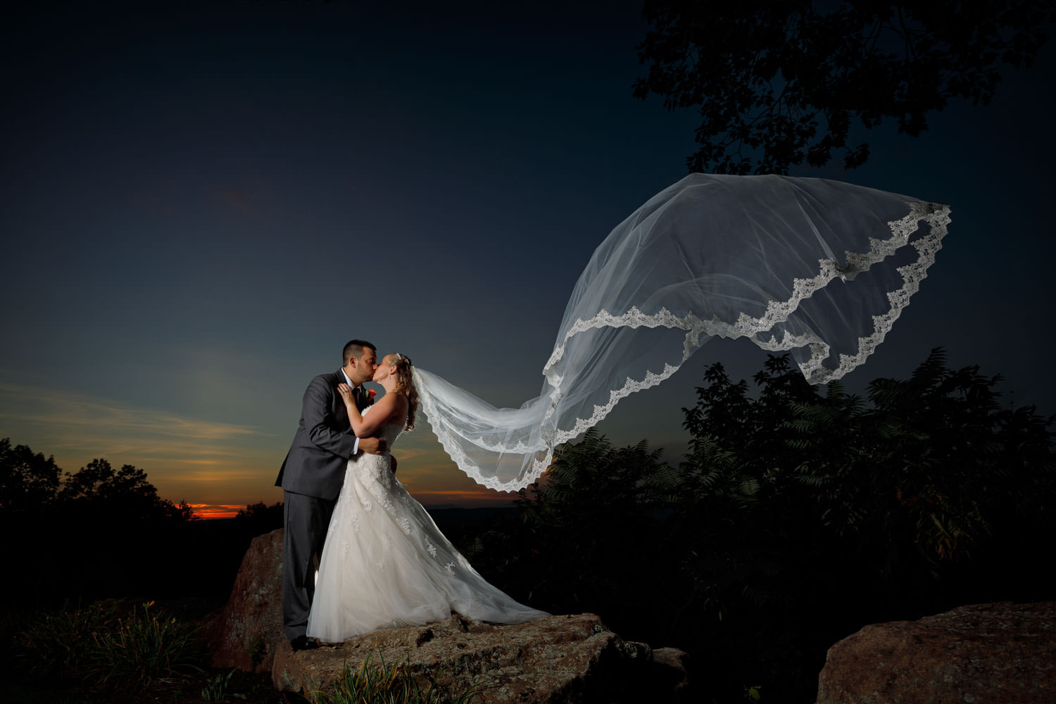 Sunset photo with Bride dipping groom with veil flowing in the wind