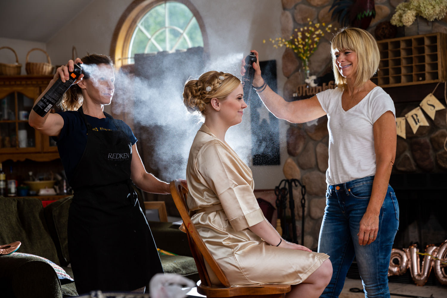 Hairdressing spaying brides hair while wearing getting ready robe