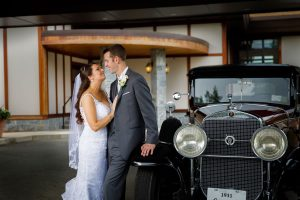 Bride and groom starring into each others eyes while holding each other and leaning on a 1931 Cadillac