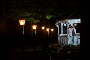 Groom Kissing bride on forehead in gazebo with lights leading toward them