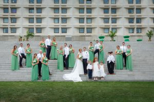 Full wedding party photo on stairs in front of Umass Amherst Hotel in background