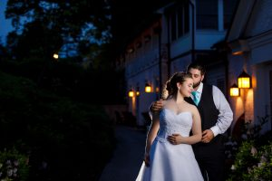 Groom kissing bride on forehead with venue lights in background