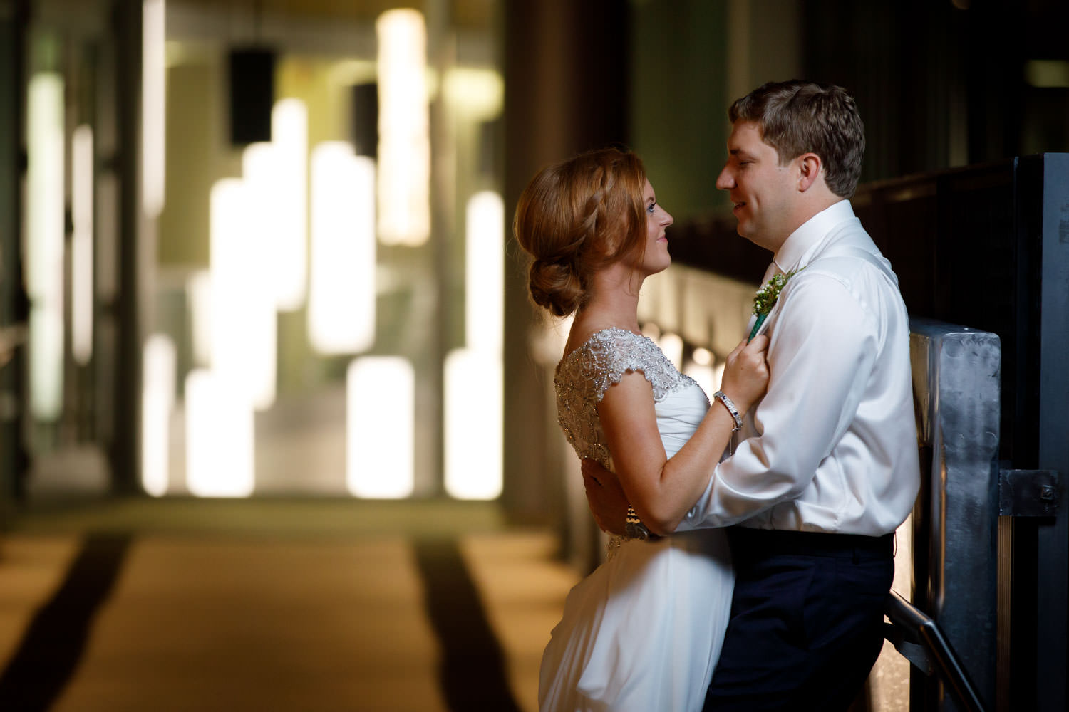 Red haired bride holding groom by suspenders in front of glass building