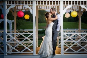 Bride and Groom Kissing in the gazebo at the Salem Cross Inn with Chinese Lanterns in background