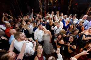 Bride and Groom surrounded by guests on dance floor at the end of night.
