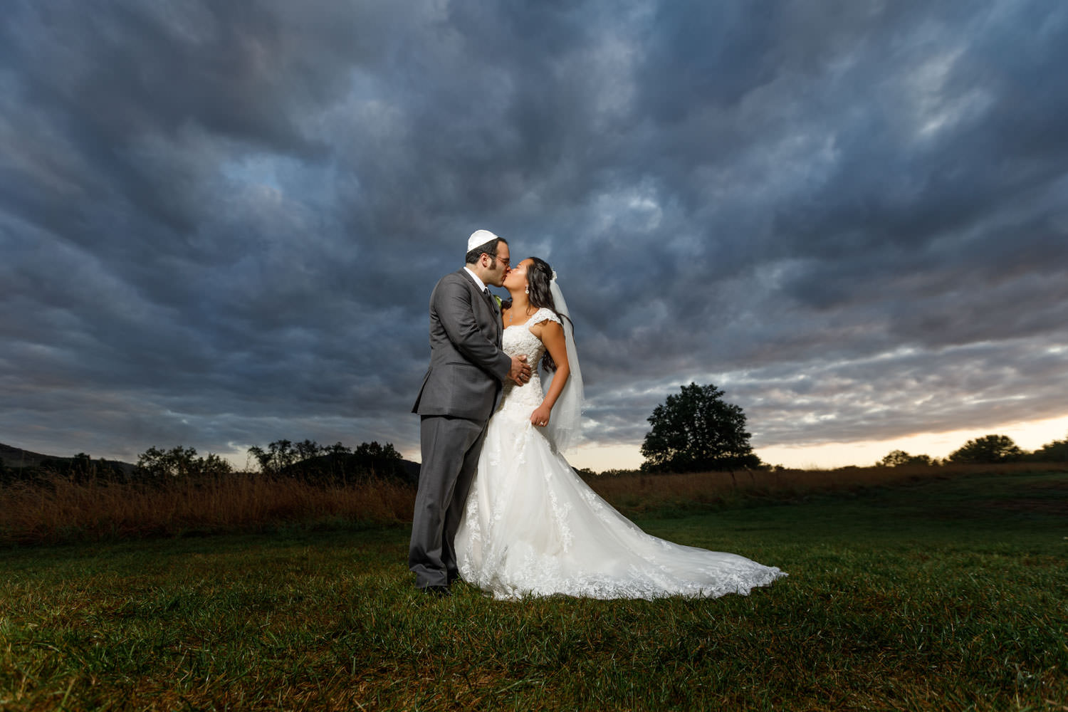 Groom with yamaka kissing bride in field with dramatic sky in background
