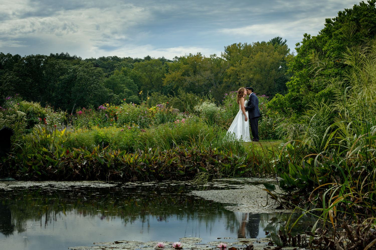Bride and Groom in garden with reflection in pond