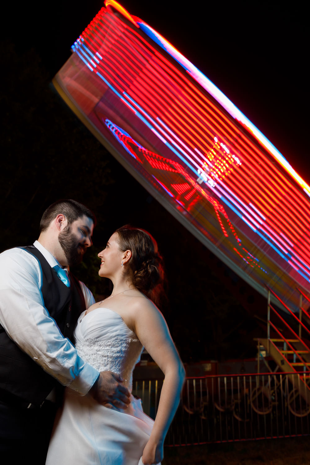 Bride and Groom looking into each others eyes with spinning tilt-a-wheel in background