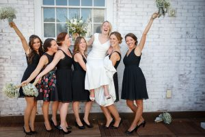 Bridesmaids holding up Bride and cheering