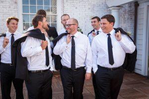 Groom and groomsmen walking with suit jacket over