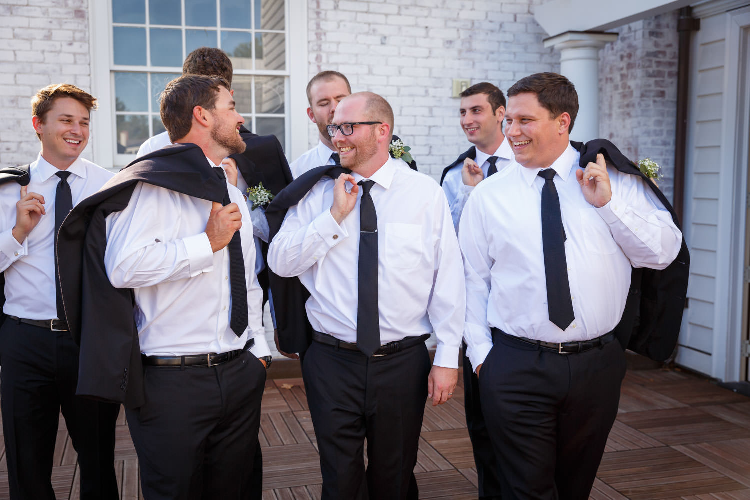 Groom and groomsmen walking with suit jacket over