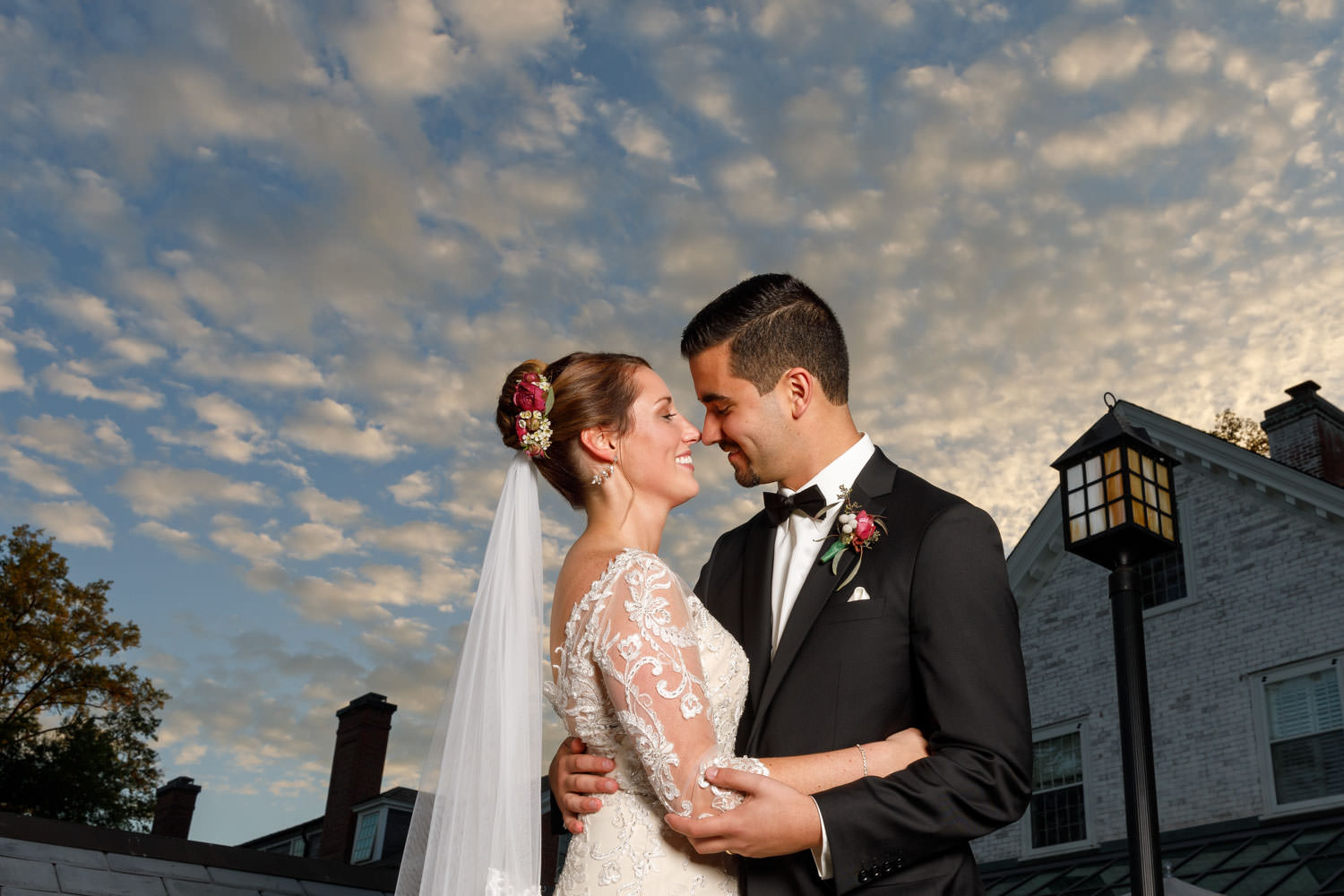 Bride and groom with puffy clouds and Inn on Boltwood in background