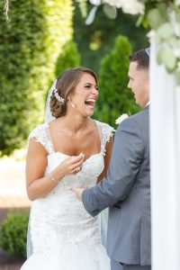 Bride with big laugh during ceremony with Jewish groom