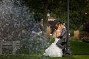 Bride kissing groom leaning against light pole with water fountain spaying in the foreground
