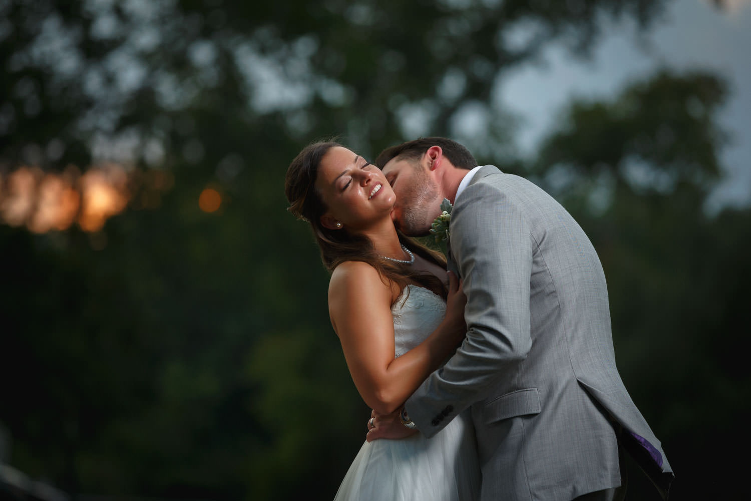 Bride leaning back while groom is kissing her neck with blurred background