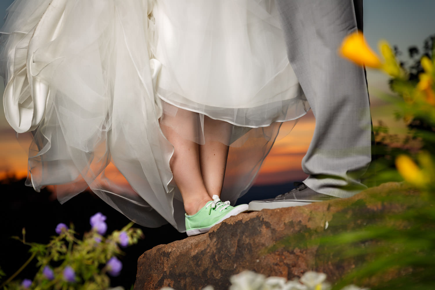Quirky photo of bride and groom Keds tennis shoes with sunset background