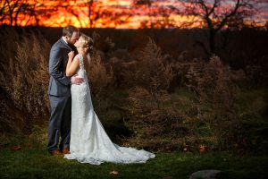 Bride and groom kissing with fiery sunset.