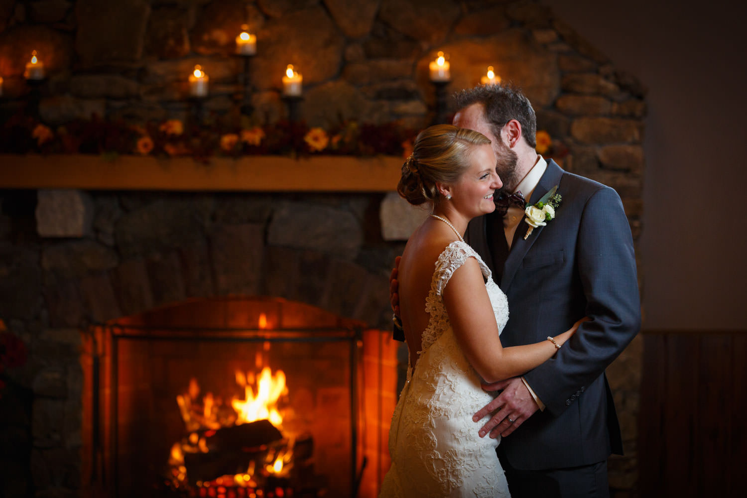 Bride and groom smiling together with fireplace and fire in the background