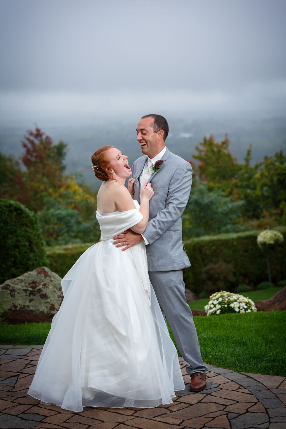 Bride and groom holding each other while laughing and overcast sky in background.