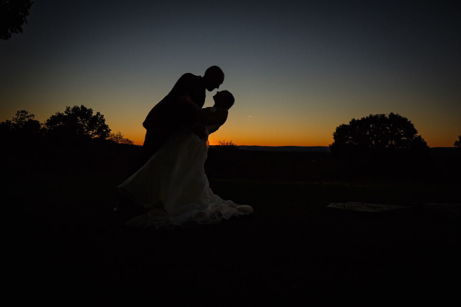 Groom dipping bride at sunset in a silhouette