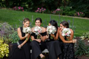 Bridesmaids in elegant black dresses peaking over flower bouquets