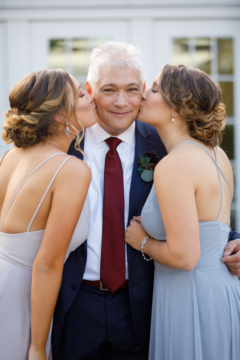 Groom getting kissed on both cheeks by both daughters