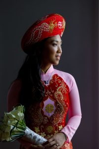 Beautiful bride in Vietnamese wedding gown with wedding bouquet bathed in beautiful natural light