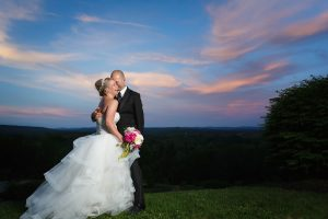 The most amazing sunset photo with bride and groom and bride laughing.