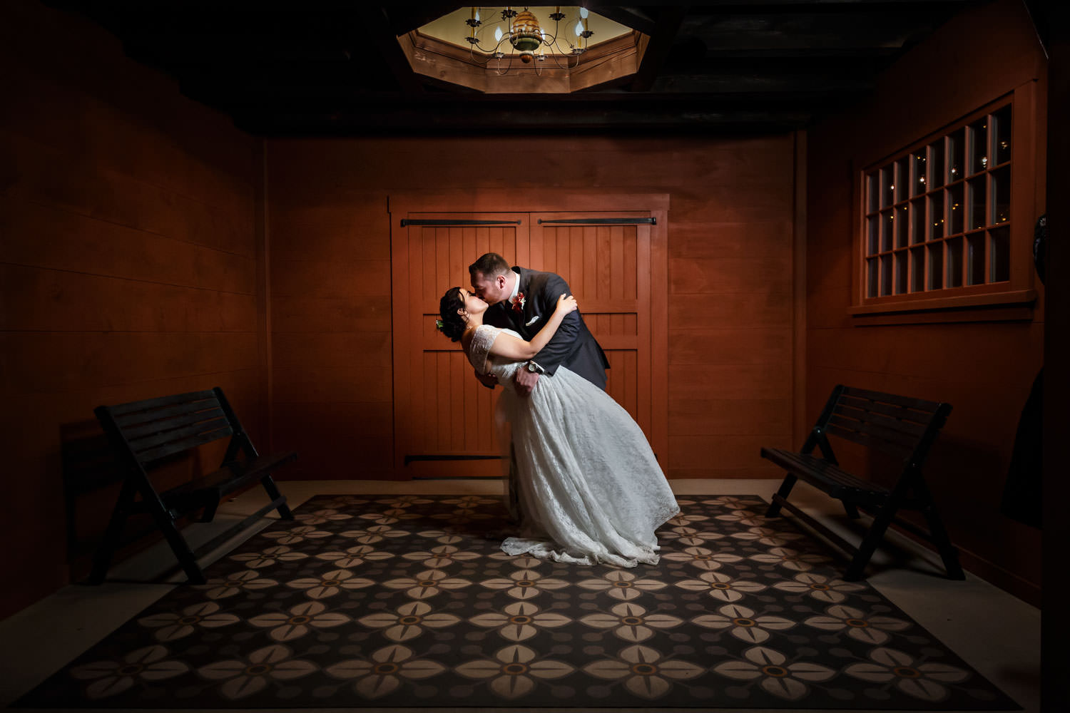 Night time photo of Bride and groom with groom dipping the bride and kissing in front of door to the reception