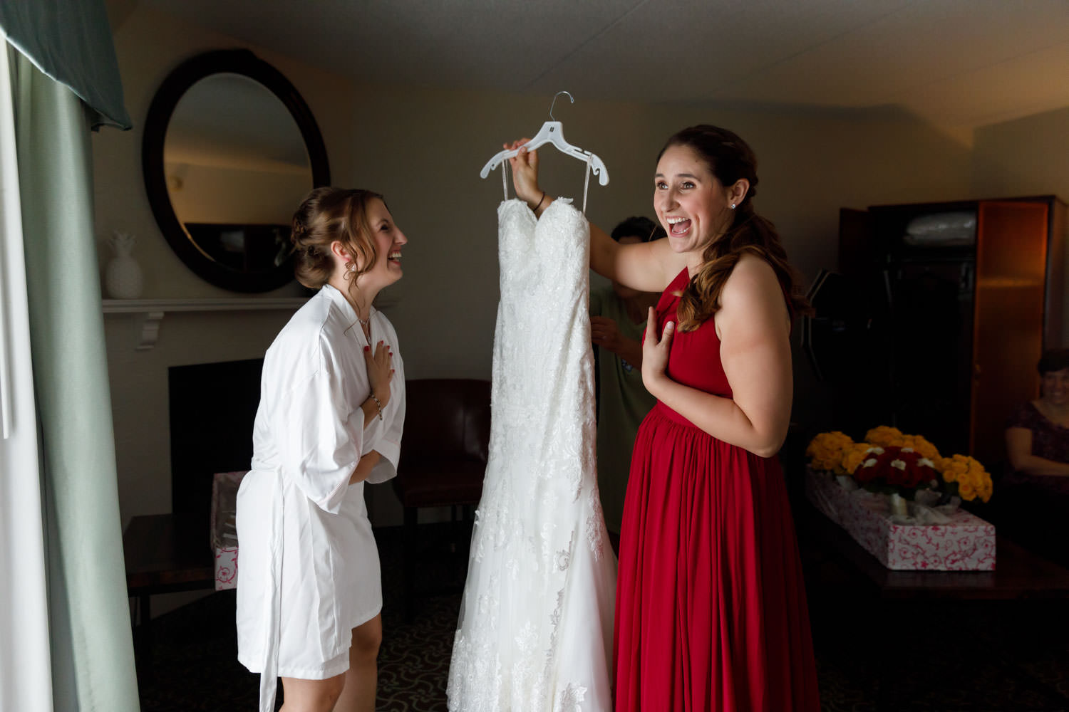 Bride and maid of honor holding wedding dress and laughing