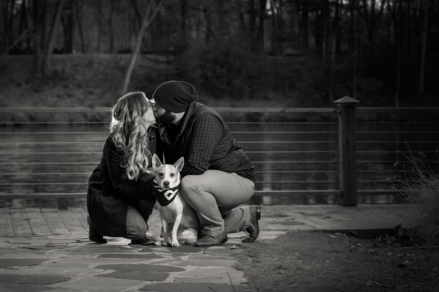 Engaged couple kissing with puppy in front of them