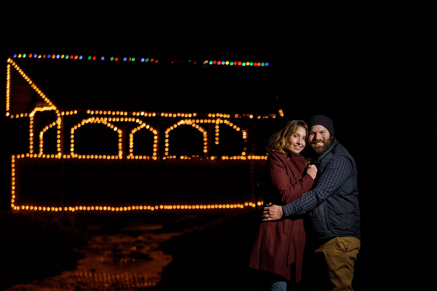 Engaged couple at night outside with Christmas lights on covered bridge