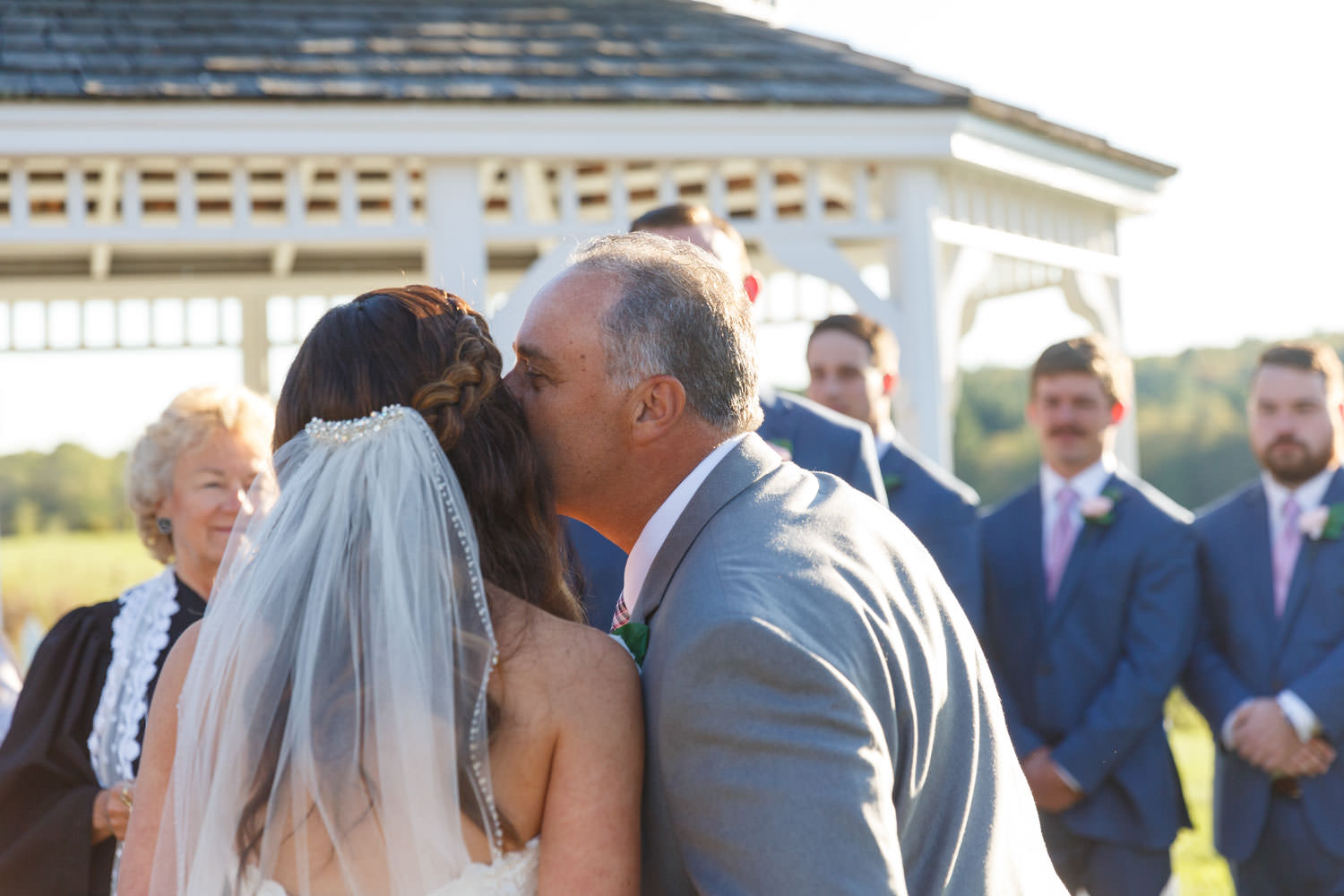 Father of the bride, kissing bride on cheek as he gives her away