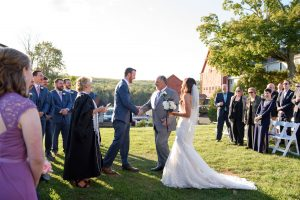 Father of the bride, shaking grooms hand during outdoor ceremony